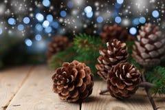 Montón de los conos del pino y de la rama de árbol de abeto en la tabla de madera rústica Papá Noel en un trineo Foto de archivo