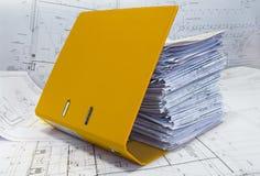 Montón de los gráficos del proyecto en carpeta amarilla. fotografía de archivo