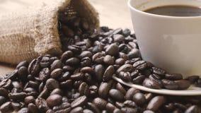 Montón de los granos de café con la taza de café almacen de video