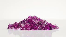 Montón de piedras violeta de la joya que vuelca el fondo blanco almacen de video