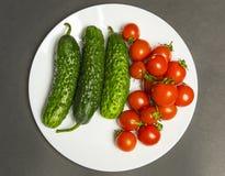 Montón de tomates y de pepinos mojados enteros imagenes de archivo