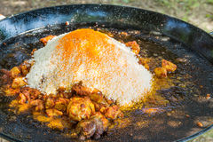 Montón del arroz crudo seco en la cacerola plana grande lista para ser mezclado con las especias de la carne del pollo frito y la Fotografía de archivo