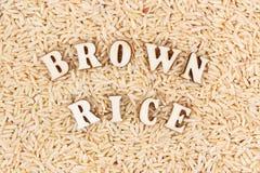 Montón del arroz moreno con la inscripción como fondo, concepto libre de la comida del gluten sano Fotografía de archivo libre de regalías