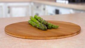 Montón del espárrago verde fresco en la placa Cámara giratoria con la cocina blanca en el fondo Carro-tiro metrajes