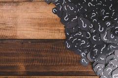 Montón del papel negro con el SIGNO de INTERROGACIÓN en la tabla de madera Fotografía de archivo libre de regalías