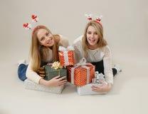 Montón feliz del abrazo de dos mujeres de las cajas de regalo Imágenes de archivo libres de regalías