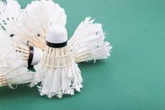 Montões da peteca usada e gastada do badminton no cour verde Imagens de Stock