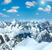 Mont Blanc mountain massif sunshiny view from Aiguille du Midi. Mont Blanc mountain massif summer snowy sunshiny landscape with blue cloudy sky view from Stock Images