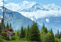 Mont Blanc mountain massif (view from Plaine Joux outskirts) and. Mont Blanc mountain massif and family on stone (France, view from Plaine Joux outskirts Royalty Free Stock Image