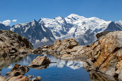 Mont Blanc reflected in a small lake. On a bright, sunny summer day the Mont Blanc mountain range France is reflected in a small lake surrounded by rocks Stock Photography