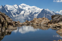 Mont Blanc reflected in a small lake. On a bright, sunny summerday the Mont Blanc mountain range France is reflected in a small lake surrounded by rocks Royalty Free Stock Photography