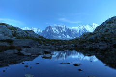 Mont Blanc under moonlight, Alps. Long exposure of Mont Blanc Massif reflecting in the small Lake Flegere, above Chamonix, France after sunset, under the Royalty Free Stock Images