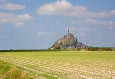 Mont Saint-Michel. Cultivated fields and Mont Saint-Michel, rocky tidal island in Normandy, France Royalty Free Stock Photos