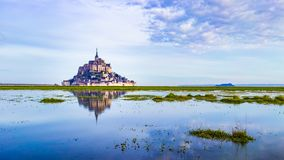 Mont-Saint-Michel reflecting in blue bay royalty free stock images