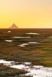 Mont Saint-Michel en la puesta del sol de una distancia Imagen de archivo