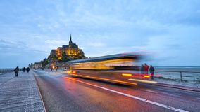 MONT SAINT MICHEL, FRANCE - September 26, 2017: View on the famo. Us Mont Saint Michel island with motion blurred shuttle bus designed for transporting tourists Royalty Free Stock Images