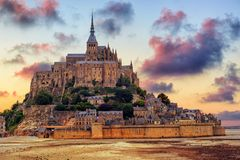 Mont Saint Michel island, Normandy, France, on sunset. Le Mont Saint Michel island, one of the most visited historical sites in France, on dramatic sunset Royalty Free Stock Images