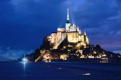 Mont Saint-michel lit up at night dark under view sky clouds perspective royalty free stock photo