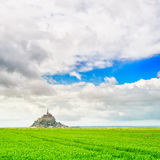 Mont Saint Michel monastery landmark and green field. Normandy, France Royalty Free Stock Image