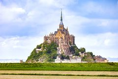 Mont Saint Michel monastery landmark and green field. Normandy, Royalty Free Stock Images