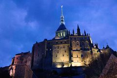 Mont saint michel monastery at night lit from beneath sunset spooky gothic stock photos