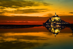 Mont Saint Michel at sunset, France. Mont Saint Michel reflected in the bay at an hot summer sunset, France Royalty Free Stock Image