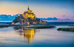 Mont Saint-Michel in twilight at dusk, Normandy, France. Panoramic view of famous Le Mont Saint-Michel tidal island in beautiful twilight during blue hour at Stock Photos