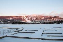 MONT-TREMBLANT,魁北克,加拿大- 2017年12月28日:滑雪胜地冬天风景与冻湖、滑雪倾斜、船坞和蓝天的 库存图片