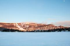 MONT-TREMBLANT,魁北克,加拿大- 2017年12月28日:滑雪胜地冬天风景与冻湖、滑雪倾斜、蓝天和月亮的 库存照片