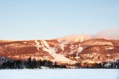 MONT-TREMBLANT,魁北克,加拿大- 2017年12月28日:滑雪胜地冬天风景与冻湖、滑雪倾斜和蓝天的 图库摄影