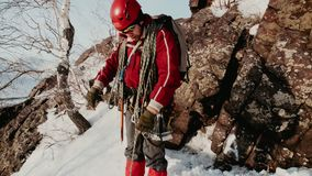 Montañés barbudo, en vidrios y casco especiales El levantarse en la cuesta nevosa de la montaña y de los vientos la cuerda cerca almacen de video