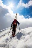 Montañés del esquí que camina para arriba a lo largo de un canto nevoso escarpado con el s fotos de archivo libres de regalías