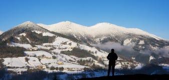 Montañés en contraluz con las montañas nevosas en el fondo, Zegama Foto de archivo libre de regalías