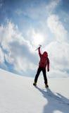 Montañés que camina cuesta arriba a lo largo de una cuesta nevosa Fotografía de archivo