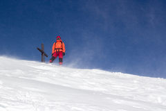 Montañés que se coloca en el top de un peack nevado Imagenes de archivo