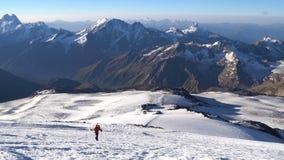 Montañés solo en los grampones que suben a la cumbre de Elbrus en las montañas del Cáucaso Pico de la nieve almacen de video