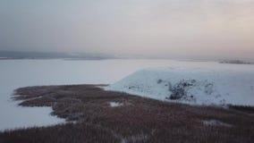 Montaña aérea de Photography Invierno Vuelo sobre el montón Vista del río congelado y de una colina grande en la orilla almacen de video