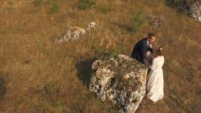 Montaña aérea de Photography Silueta del hombre de negocios Cowering Novio y muchacha cariñosos en el fondo de un prado metrajes