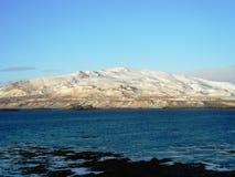 Montaña baja cubierta en nieve durante marea baja imagen de archivo