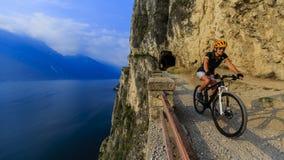Montaña biking en la mujer de la salida del sol sobre el lago Garda en la trayectoria Sentier Fotos de archivo libres de regalías