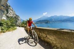 Montaña biking en la mujer de la salida del sol sobre el lago Garda en la trayectoria Sentier Imagen de archivo