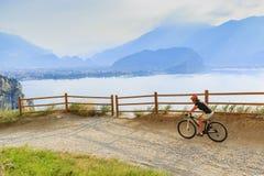 Montaña biking en la mujer de la salida del sol sobre el lago Garda en la trayectoria Sentier Fotografía de archivo