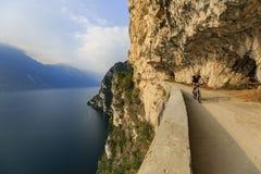 Montaña biking en la mujer de la salida del sol sobre el lago Garda en la trayectoria Sentier Fotos de archivo