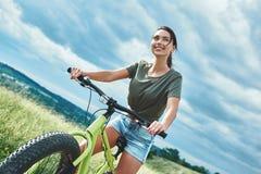 Montaña biking - la mujer con la bici disfruta de vacaciones de verano fotografía de archivo
