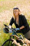 Montaña biking prados asoleados juguetones de la mujer joven Imagenes de archivo