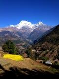 Montaña, bluesky coronados de nieve y pueblo Imagen de archivo libre de regalías