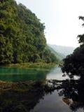 Montaña boscosa reflejada en la piscina de Semuc Champey de la turquesa Imagen de archivo libre de regalías