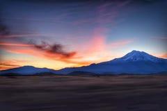 Montaña capsulada nieve con puesta del sol hermosa Imagenes de archivo