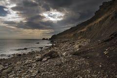 Montaña cerca del mar sol bloqueado por las nubes Rocas Fotos de archivo