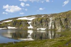 Montaña con nieve, la cascada y agua Imagen de archivo